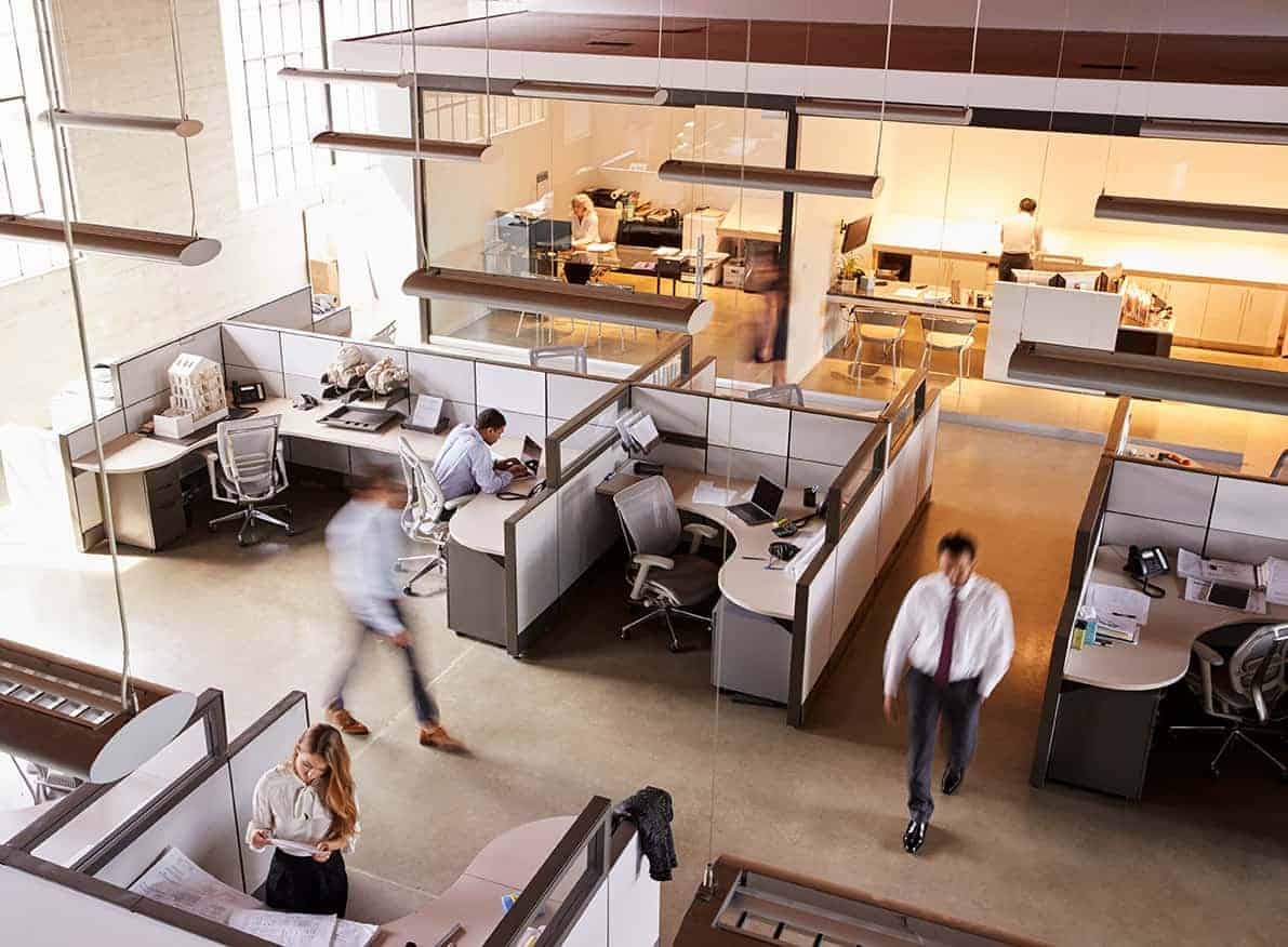 Workers walking through office of modern cubicles